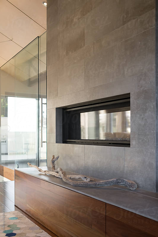 Double sided fireplace in luxurios lounge room by Rowena Naylor for Stocksy United