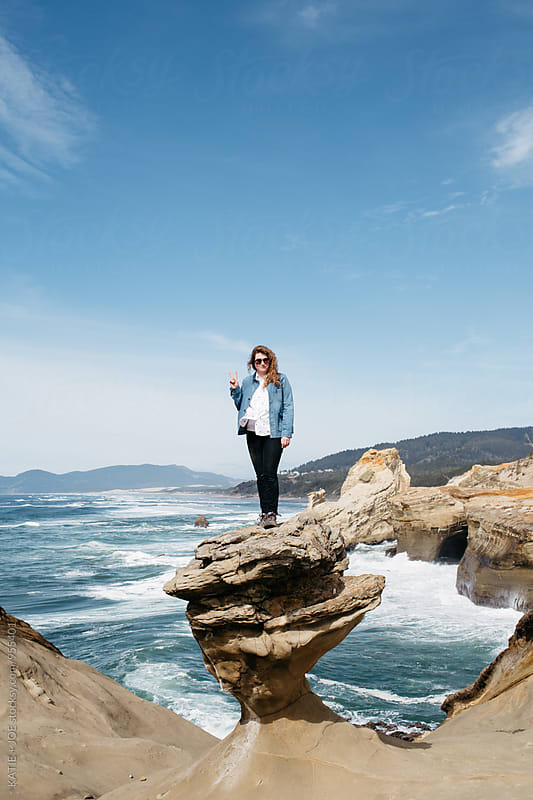 Woman standing on a rock on the coast giving a peace sign by KATIE + JOE for Stocksy United