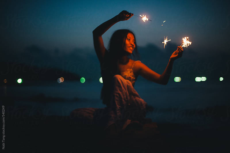 Beautiful young woman dancing by the sea with sparkler in summer night by Nabi Tang for Stocksy United