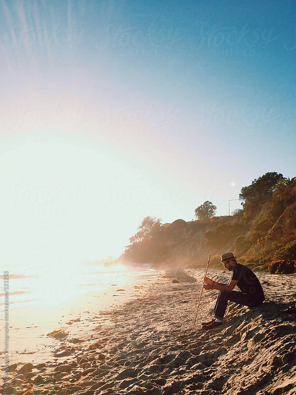 Man sitting on beach at sunset by Kristin Rogers Photography for Stocksy United