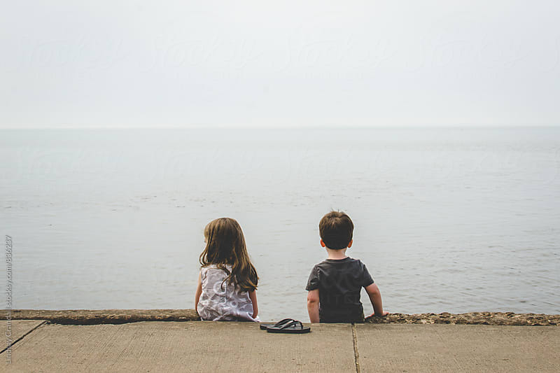 Two children looking at the sea by Lindsay Crandall for Stocksy United