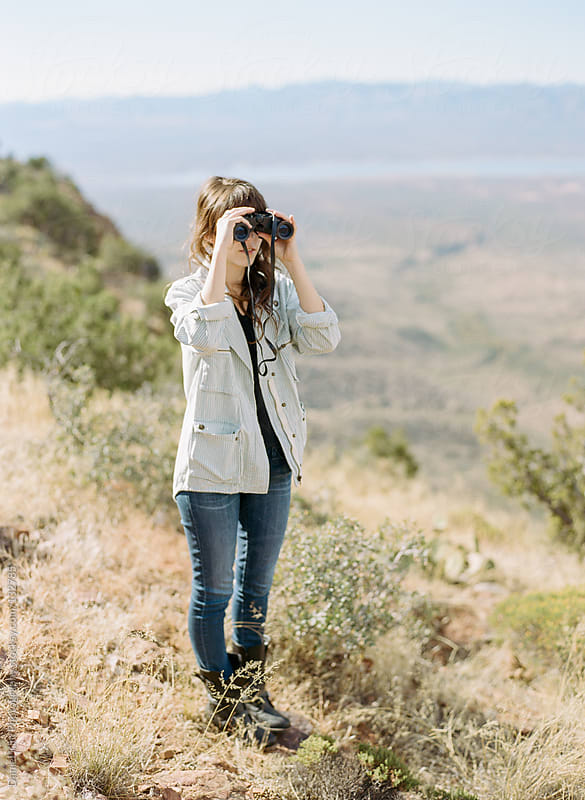 girl viewing with binoculars by Daniel Kim Photography for Stocksy United