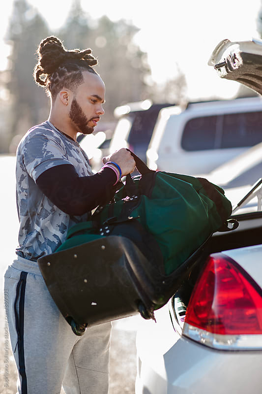 African American athlete putting his gym bag into his car by Suprijono Suharjoto for Stocksy United