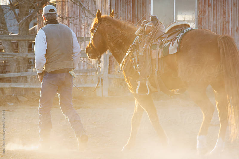 A man walks through the dust with his saddled horse by Tana Teel for Stocksy United