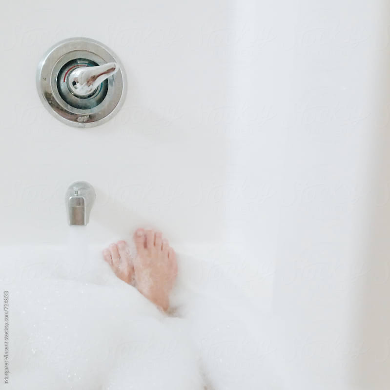 feet sticking out of a bubble bath by Margaret Vincent for Stocksy United