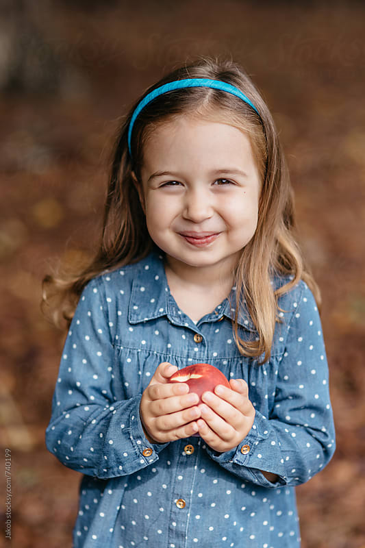 Beautiful young girl holding a nectarine  by Jakob for Stocksy United
