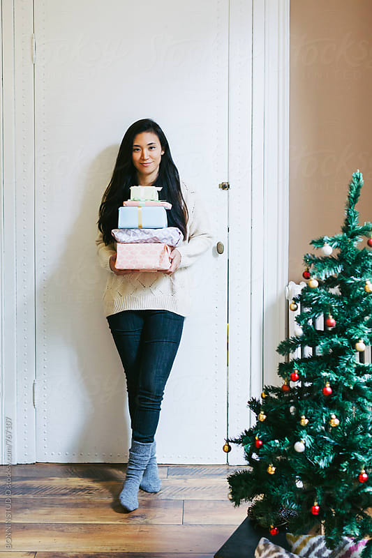 Asian woman holding Christmas presents at home. by BONNINSTUDIO for Stocksy United