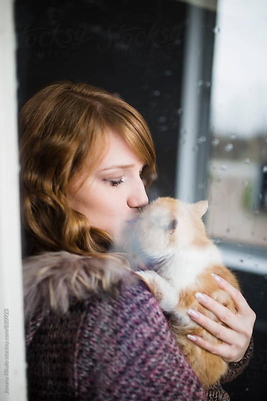 Young woman kissing her kitten by Jovana Rikalo for Stocksy United