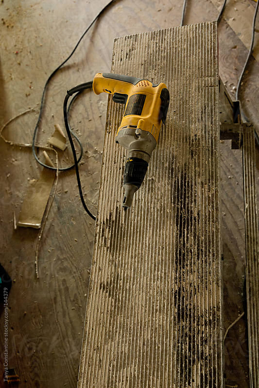 Drywall screwdriver sitting on bench at construction site by Tanya Constantine for Stocksy United