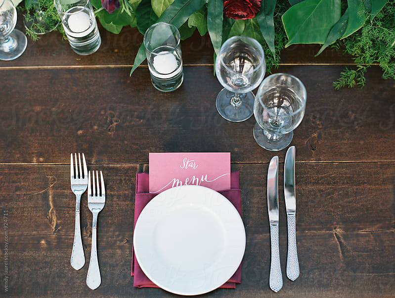 pink and wood place setting at a wedding dinner table by wendy laurel for Stocksy United