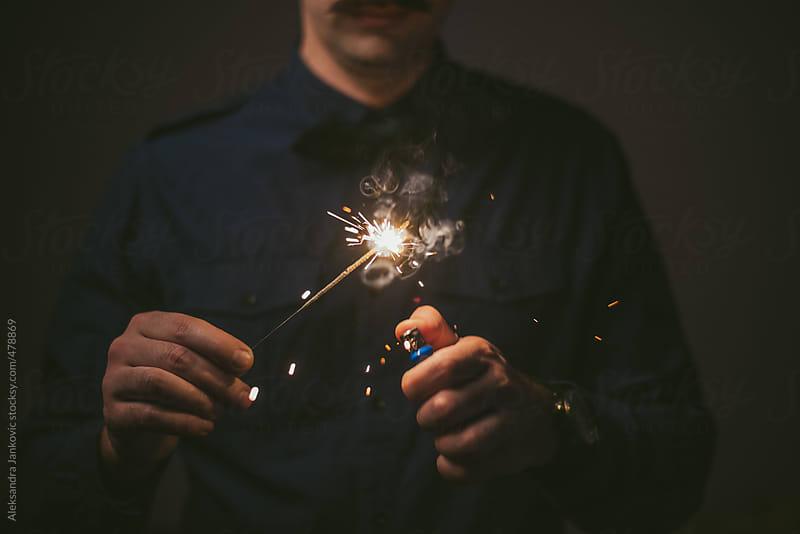 Man lights a sparkler by Aleksandra Jankovic for Stocksy United