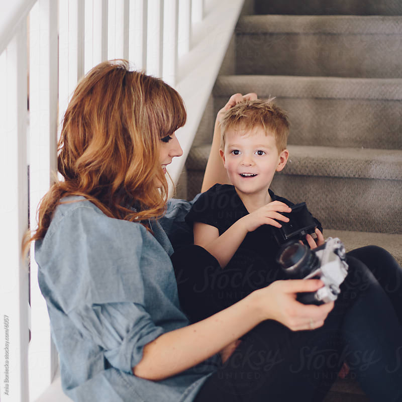 A portrait of mother and son sitting on the stairs by Ania Boniecka for Stocksy United