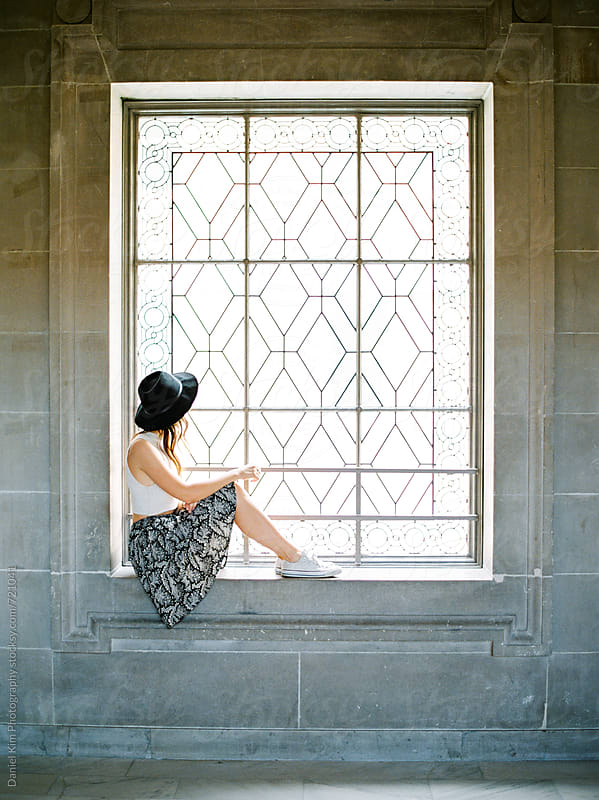 Young woman sitting in window by Daniel Kim Photography for Stocksy United