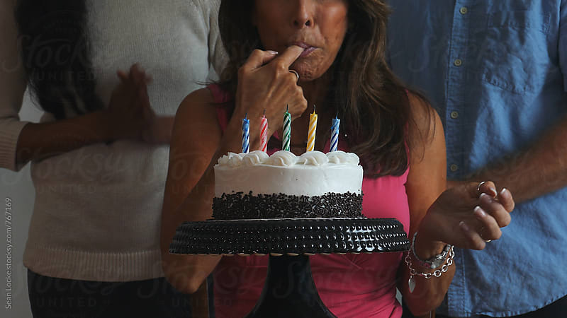 Woman Tastes Icing After Blowing Out Candles by Sean Locke for Stocksy United
