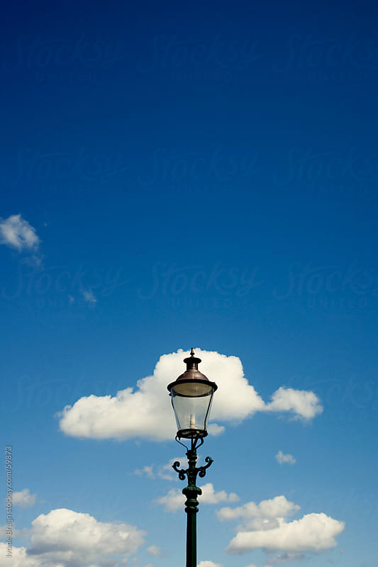 A classic lantern with a bright blue sky with some clouds by Ivo de Bruijn for Stocksy United