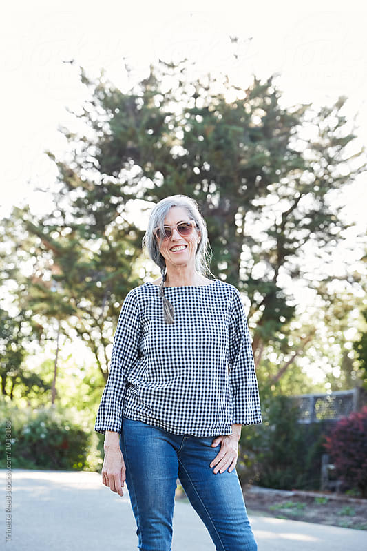 Portrait of stylish mature woman with grey hair outdoors at sunset by Trinette Reed for Stocksy United