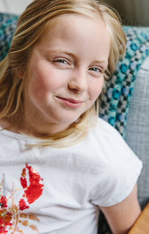 A little girl with a knowing smile. by Helen Rushbrook for Stocksy United