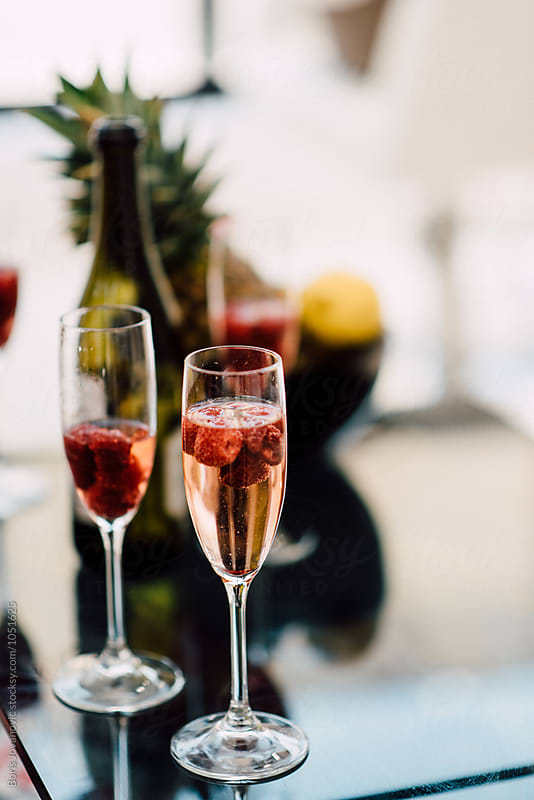Glasses filled with Champagne and fresh raspberry