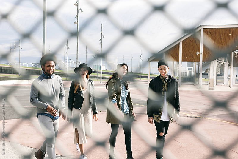 Group of multicultural friends having fun walking through a fence. by BONNINSTUDIO for Stocksy United