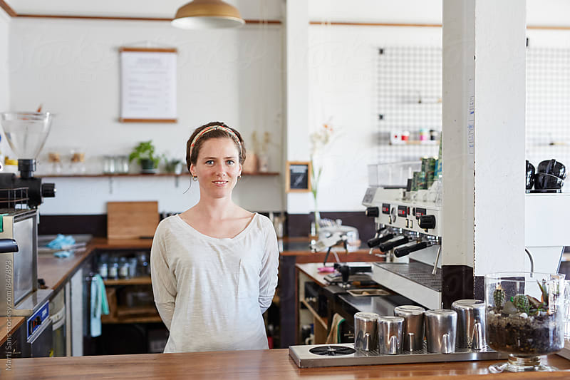 Portrait of cute woman standing in coffee shop by Martí Sans for Stocksy United