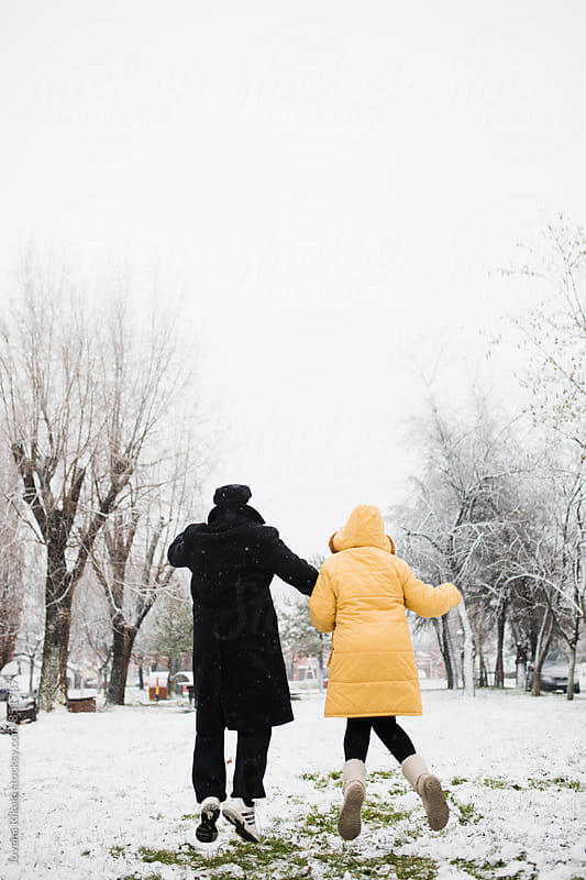 Happy old couple jumping in snow by Jovana Rikalo for Stocksy United
