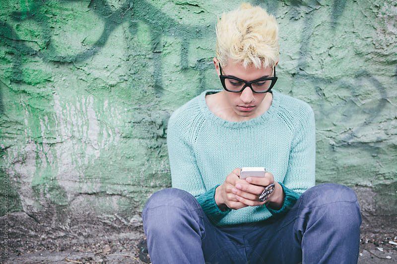 Stylish Millenial Male with Bleached Blond Hair Texting on Smart Phone Technology by Joselito Briones for Stocksy United