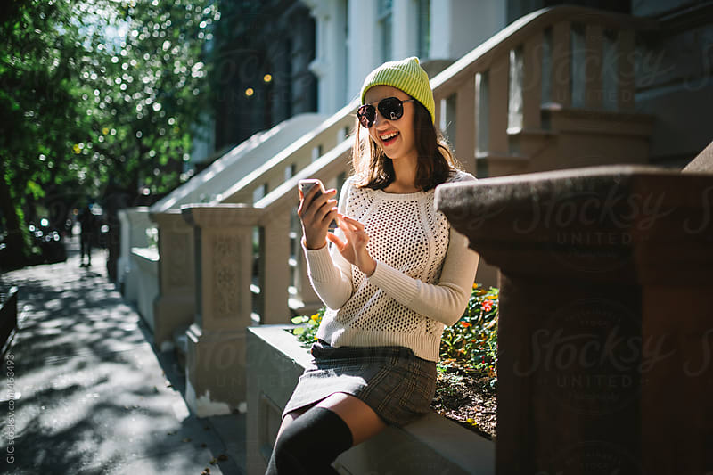 Happy woman typing on the phone by GIC for Stocksy United