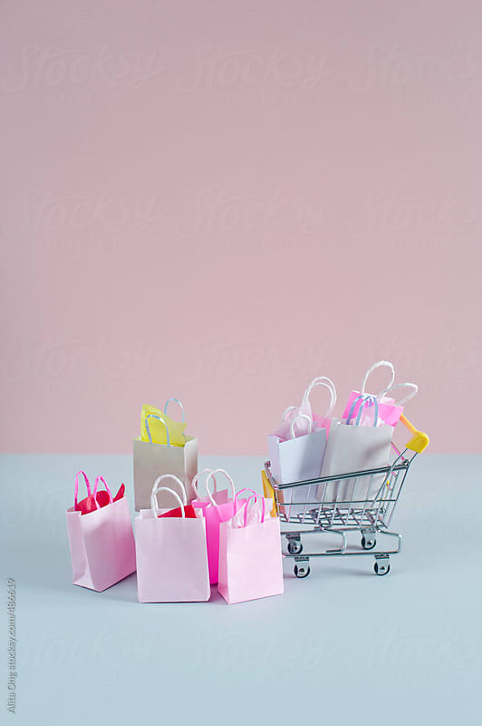 Shopping cart and colorful shopping bags by Alita Ong for Stocksy United