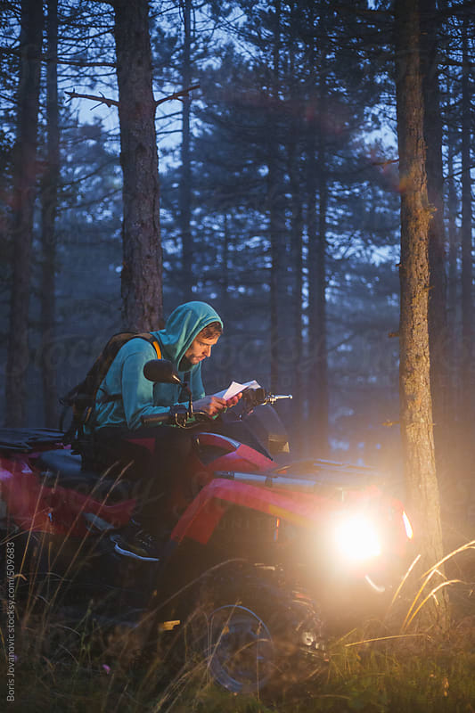Young explorer looking at map in the woods by Boris Jovanovic for Stocksy United