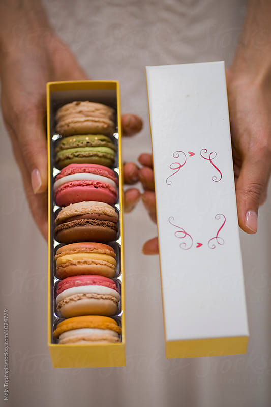 Woman holding a box with macaroons by Maja Topcagic for Stocksy United