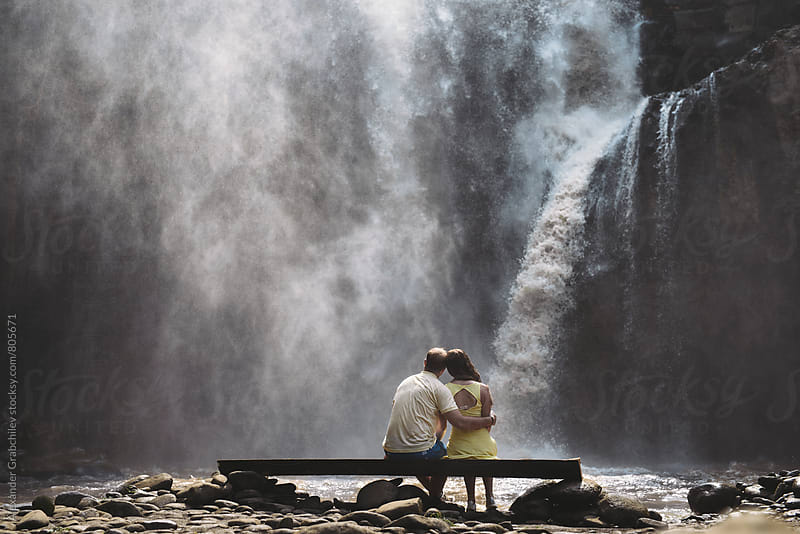 young couple sitting in front of waterfall  by Alexander Grabchilev for Stocksy United