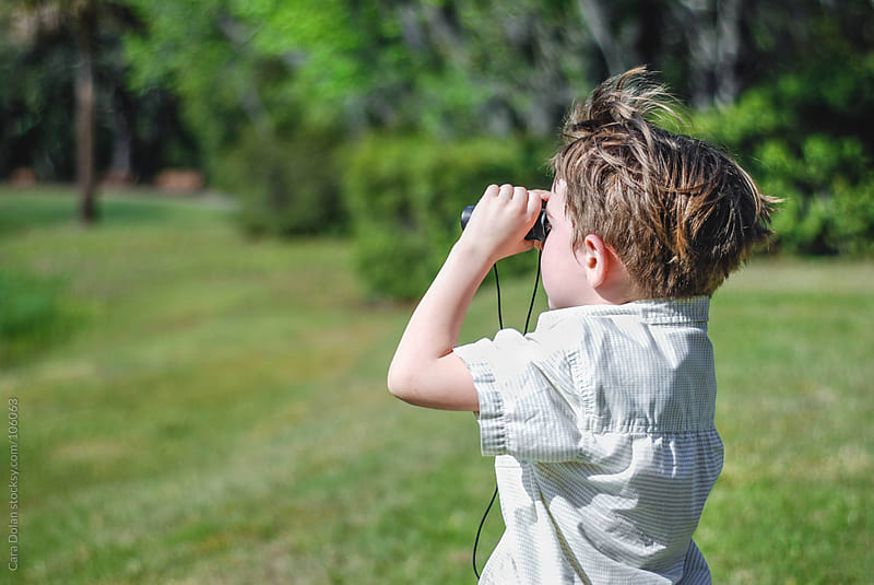 Child with binoculars is on the lookout for birds and other wildlife by Cara Dolan for Stocksy United