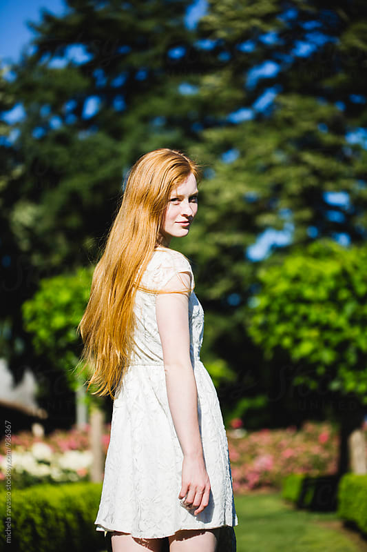 Beautiful young girl with long red hair enjoying a sunny day in the park by michela ravasio for Stocksy United