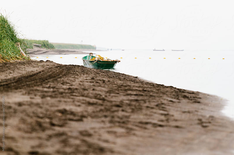 Low-angle view of a small commercial fishing skiff with a fishing net beached at a river bank by Mihael Blikshteyn for Stocksy United
