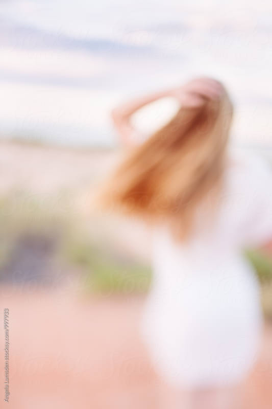 Blurred image of a girl with her hand to her windswept hair by Angela Lumsden for Stocksy United