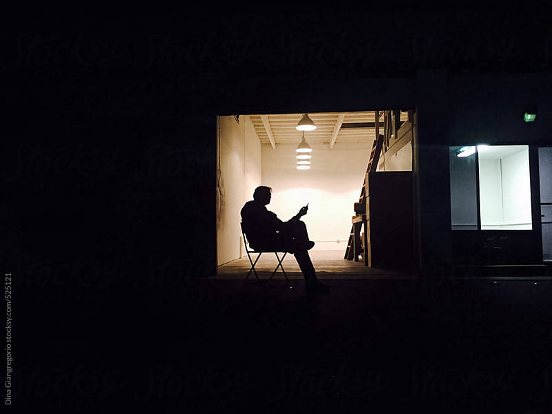 Silhouette of Man Alone in Dark Office Space Using Cellular Device by Dina Giangregorio for Stocksy United