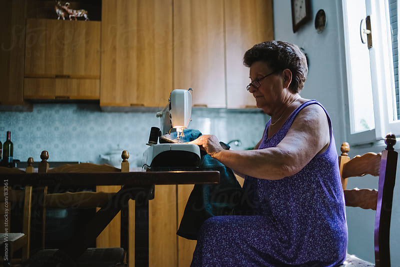 Senior woman using a sewing machine by GIC for Stocksy United
