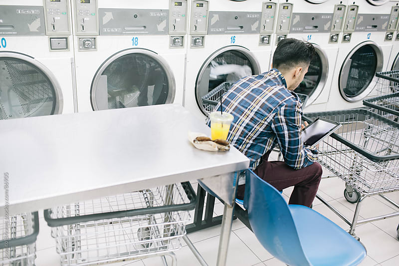 Young Man Reading e-Book in electronic tablet doing Laundry in L by Joselito Briones for Stocksy United