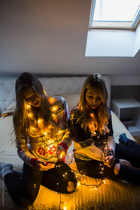Two female friends and Christmas lights by Jovana Rikalo for Stocksy United