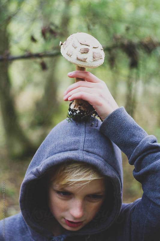 Boy with a large mushroom on his head. by Helen Rushbrook for Stocksy United