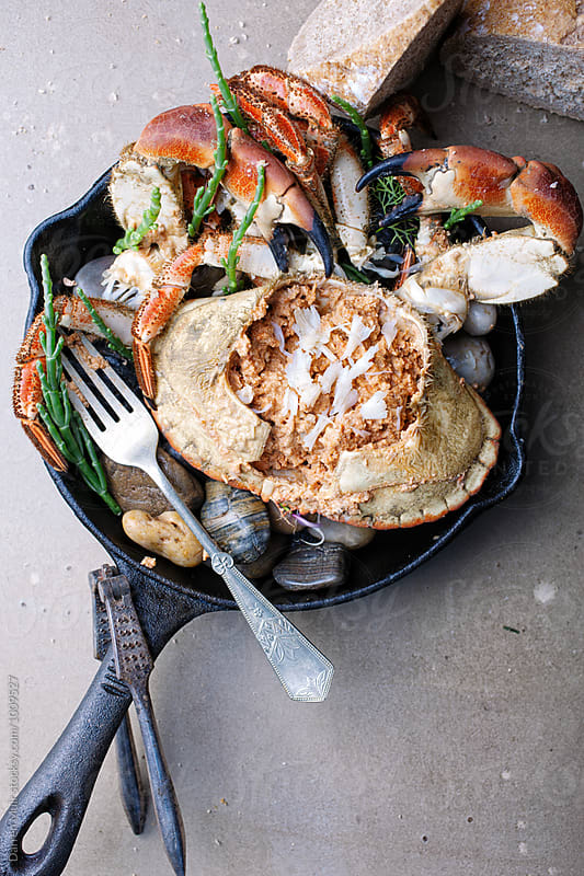 Dressed crab served with crusty bread.Crab in a skillet with samphire. by Darren Muir for Stocksy United