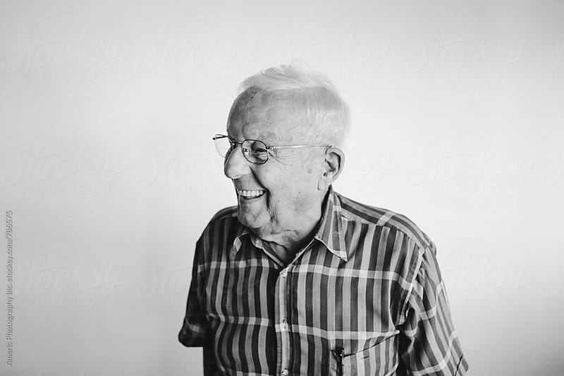 Senior man laughing candidly - on white background by Rob and Julia Campbell for Stocksy United