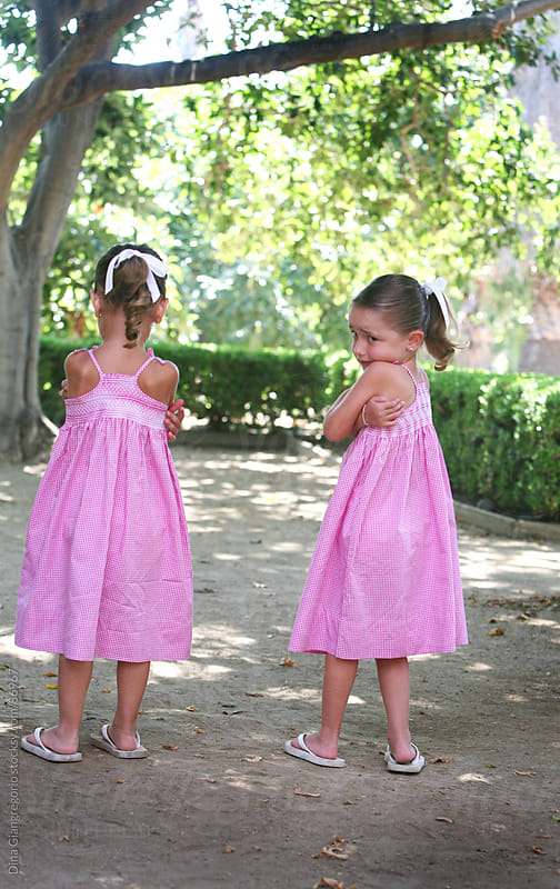 Twin Sisters pouting wearing matching dresses by Dina Giangregorio for Stocksy United