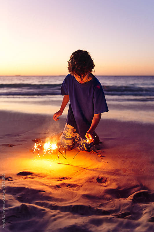 Boy lighting sparklers in the sand at the beach at night by Angela Lumsden for Stocksy United