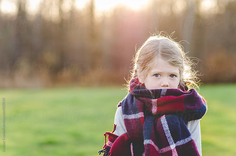 Girl wrapped in plaid scarf by Lindsay Crandall for Stocksy United