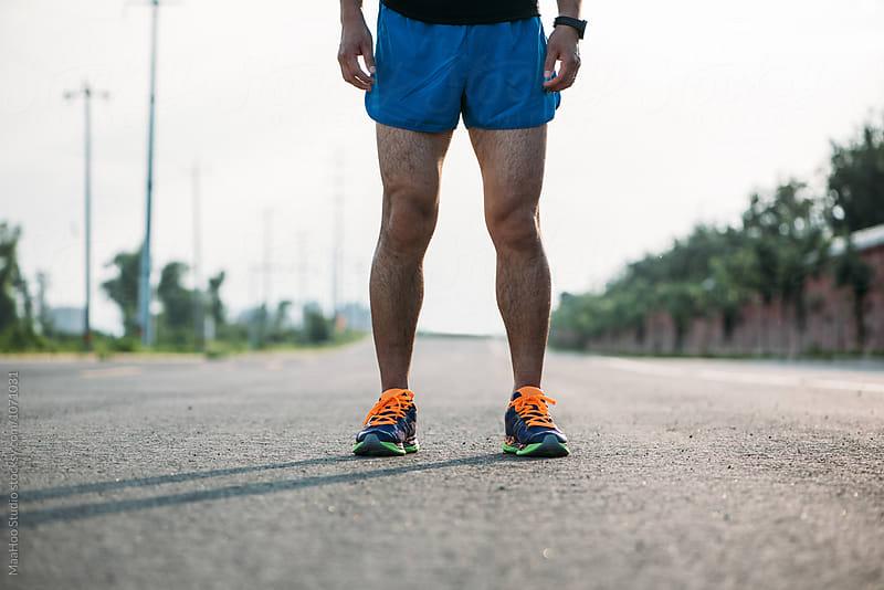 Runner standing on road by MaaHoo Studio for Stocksy United