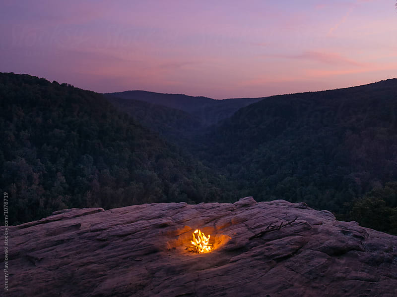 Colorful sunset while camping on cliff. Campfire on rock. by Jeremy Pawlowski for Stocksy United
