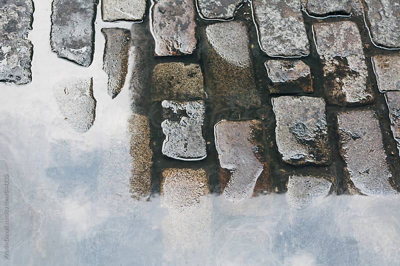 Puddle on cobblestone street by Kristin Duvall for Stocksy United