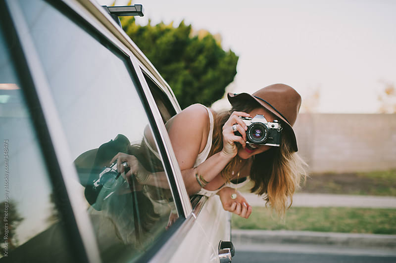 Pretty girl hanging out of car window playing with camera by Kristin Rogers Photography for Stocksy United