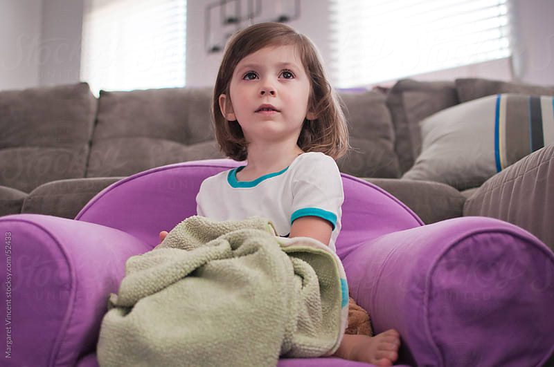 a little girl sits in her purple armchair and watches attentively by Margaret Vincent for Stocksy United